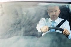 Homme d'affaires conduisant le véhicule avec le ciel sur le pare-brise Image stock