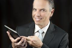 Homme d'affaires confiant UsesTablet Photographie stock libre de droits
