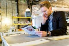 Homme d'affaires confus lisant le journal dans un restaurant images libres de droits