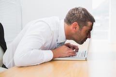 Homme d'affaires confus regardant son ordinateur portable Photo stock