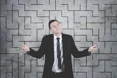 Homme d'affaires confus sur le fond compliqué de dessin de labyrinthe photos stock
