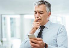Homme d'affaires confus utilisant un téléphone intelligent photo stock