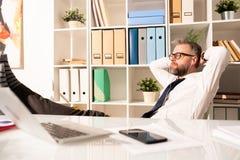 Homme d'affaires contemplatif écoutant le dossier audio dans des écouteurs photographie stock