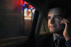 Homme d'affaires contemplatif au téléphone dans le siège arrière d'une voiture regardant la nuit dans Pékin Images stock