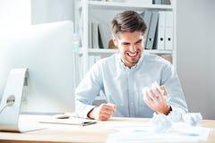 Homme d'affaires contrarié fol travaillant et papier de froissement dans le bureau Images stock