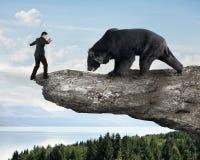 Homme d'affaires contre l'ours noir équilibrant sur la falaise avec des arbres de ciel Photo libre de droits