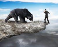 Homme d'affaires contre l'ours noir équilibrant sur la falaise avec le nuage de ciel Photos stock