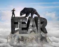 Homme d'affaires contre l'ours noir se tenant sur le mot de béton de la crainte 3D Images stock