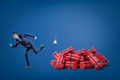 Homme d'affaires courant à partir du paquet de bâtons rouges de dynamite de tnt avec le fusible allumé sur le fond bleu illustration de vecteur