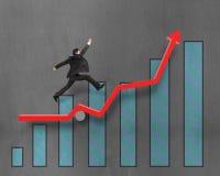Homme d'affaires courant et sautant sur la flèche rouge de croissance avec le diagramme Photographie stock libre de droits