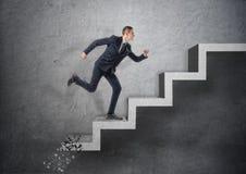 Homme d'affaires courant l'escalier en béton, qui écrase vers le bas après lui Photographie stock libre de droits