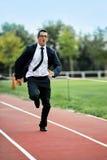 Homme d'affaires courant rapidement sur la voie sportive dans des contraintes du travail et le concept d'urgence Photographie stock libre de droits