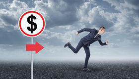 Homme d'affaires courant sur l'asphalte et le panneau routier avec le dollar image stock