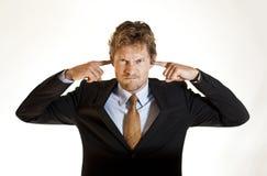 Homme d'affaires couvrant ses oreilles Photo libre de droits