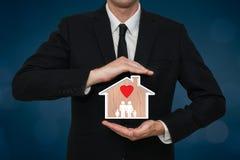 Homme d'affaires couvrant une maison à la maison de famille avec amour Concept de protection et sécurité avec le fond bleu Photographie stock