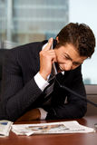 Homme d'affaires criant au téléphone dans un bureau Photo stock
