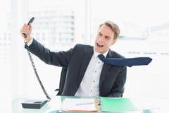 Homme d'affaires criant comme il donne le téléphone au bureau Image libre de droits