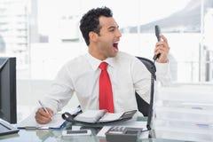 Homme d'affaires criant comme il donne le téléphone au bureau Photos libres de droits