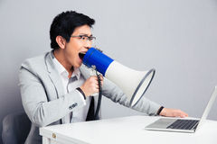 Homme d'affaires criant dans le mégaphone sur l'ordinateur portable Photographie stock libre de droits