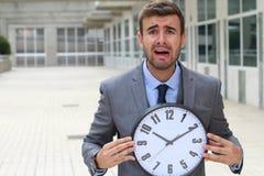 Homme d'affaires criant tout en tenant une grande horloge Photo stock