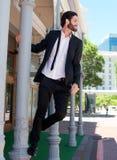 Homme d'affaires décontracté heureux se tenant dessus sur le poteau dehors photos libres de droits