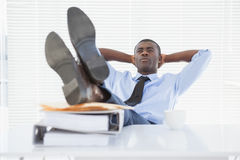 Homme d'affaires décontracté s'asseyant dans sa chaise avec des pieds  photo stock