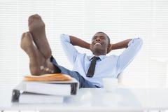 Homme d'affaires décontracté s'asseyant dans sa chaise avec des pieds  image stock