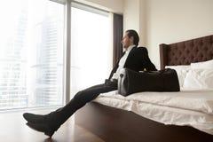 Homme d'affaires décontracté s'asseyant sur le lit sans compter que le sac de bagage image libre de droits
