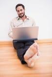Homme d'affaires décontracté s'asseyant sur le plancher tout en à l'aide de l'ordinateur portable Photo libre de droits