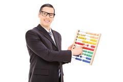 Homme d'affaires déplaçant les unités d'un abaque Photo stock