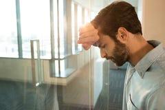 Homme d'affaires déprimé se penchant sur le verre image libre de droits