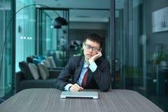 Homme d'affaires déprimé seul s'asseyant dans le bureau photos stock