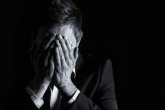 Homme d'affaires désespéré couvrant son visage. Photographie stock