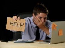 Homme d'affaires désespéré fatigué dans l'effort fonctionnant au bureau d'ordinateur de bureau tenant le signe demandant l'aide photos libres de droits