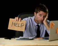 Homme d'affaires désespéré fatigué dans l'effort fonctionnant au bureau d'ordinateur de bureau tenant le signe demandant l'aide image libre de droits