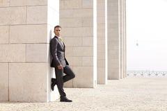 Homme d'affaires détendant à côté d'un certain mur Image stock