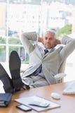 Homme d'affaires détendant à son bureau Photos stock