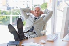 Homme d'affaires détendant au bureau et souriant à l'appareil-photo Image stock