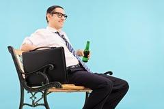 Homme d'affaires détendant avec de la bière sur le fond bleu Image stock