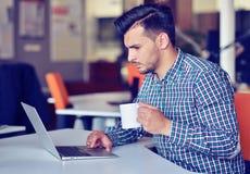 Homme d'affaires détendant avec des jambes sur le bureau, café potable tout en rêvant de l'avenir sur le lieu de travail dans le  Photo libre de droits