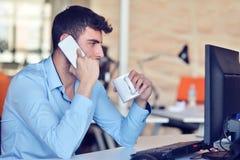 Homme d'affaires détendant avec des jambes sur le bureau, café potable tout en rêvant de l'avenir sur le lieu de travail dans le  Photographie stock