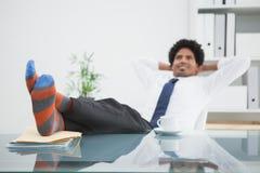 Homme d'affaires détendant dans sa chaise pivotante avec des pieds  Photographie stock libre de droits