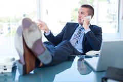 Homme d'affaires détendant dans une chaise pivotante et ayant un appel téléphonique Photos stock