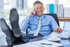 Homme d'affaires détendant dans une chaise pivotante et ayant un appel téléphonique Image libre de droits