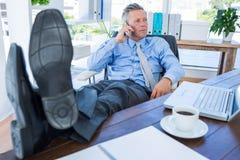 Homme d'affaires détendant dans une chaise pivotante et ayant un appel téléphonique Photos libres de droits