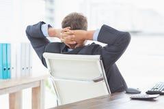 Homme d'affaires détendant dans une chaise pivotante se penchant de retour Photo libre de droits