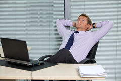 Homme d'affaires détendant sur la chaise avec l'ordinateur portable sur le bureau Image libre de droits