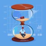 Homme d'affaires d'afro-américain à l'intérieur de concept de gestion du temps de date-butoir d'horloge de montre de sable Photos libres de droits