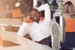 Homme d'affaires d'afro-américain s'asseyant à l'ordinateur dans le bureau de démarrage Images libres de droits