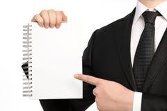 Homme d'affaires d'isolement tenant un carnet ou un morceau de papier Photographie stock libre de droits